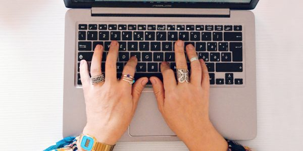 Mani che battono sulla tastiera del computer per cercare prodotti su uno shop online