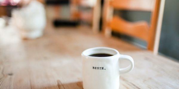 """Un tavolo con una tazza di caffè su cui c'è scritto """"Begin"""", cioè """"Comincia""""."""